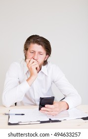 stressed young business employee sitting at office and texting using his smartphone