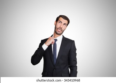 Stressed young business man pulling his own neck shirt.