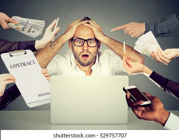 Stressed young business man sitting at table in office working on computer overwhelmed by errands should be done. Busy day of an employee concept