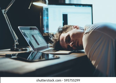 stressed young business man sleeping on his laptop in his office