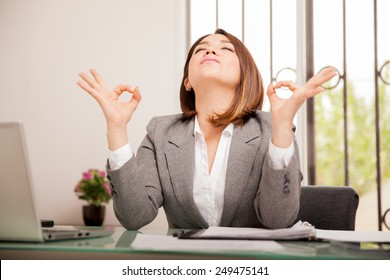 Stressed young business woman doing some breathing exercises and meditating at her office