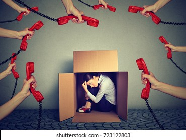 Stressed young business woman sitting hiding in a box overwhelmed by too many telephone calls and errands should be done. Busy day of an employee concept
