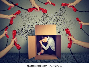 Stressed young business woman sitting hiding in a box overwhelmed by too many red telephone calls and errands should be done. Busy day of an employee concept
