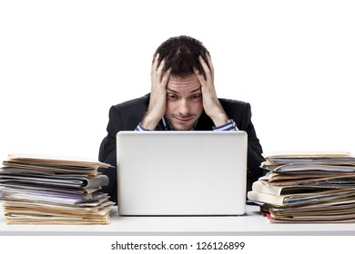 Stressed young businessman with head in hand