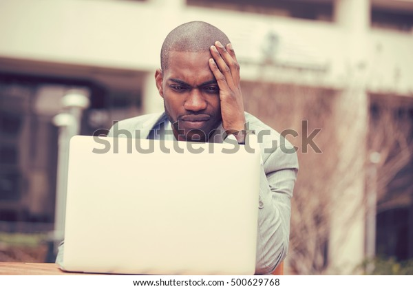 stressed young businessman sitting outside corporate office working on laptop computer holding head with hand looking down. Negative human emotion facial expression feelings.