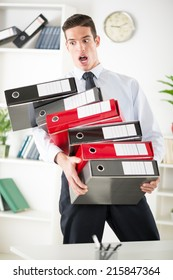 Stressed young Businessman standing in the office and holding many binders. They're spilling out hand.