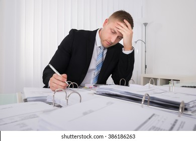 Stressed Young Businessman Working Late In Office