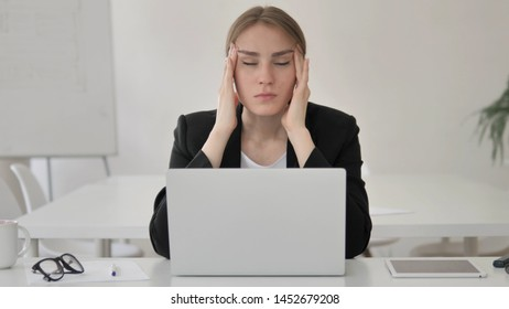 Stressed Young Businesswoman with Headache Working on Laptop