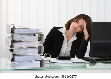 Stressed Young Businesswoman Looking At Stack Of Folders In Office