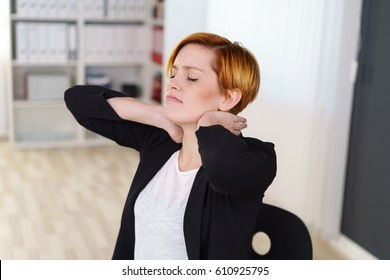 Stressed young businesswoman rubbing her neck as she stretches to relieve the tension with her eyes closed