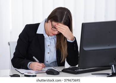 Stressed Young Businesswoman Sitting In Office With Financial Report