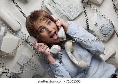 Stressed  young businesswoman with telephones in her hands.