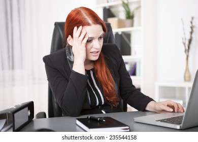 Stressed young businesswoman working on laptop