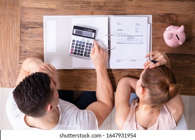 Stressed Young Couple Looking At Invoice On Wooden Desk