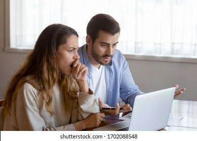 Stressed young couple sitting at table, looking at laptop screen. Millennial man woman shocked by negative cash balance, checking banking online application on laptop, receiving bad news notification.