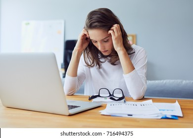 stressed young entrepreneur holding her head and looking down because of stress and headache in office