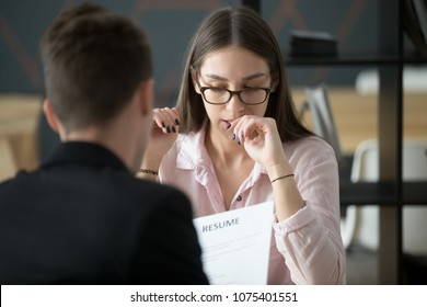 Stressed young female applicant feeling nervous at job interview while hr reading resume, unprepared candidate worried biting nails afraid of bad result at hiring negotiations, fear of fail concept
