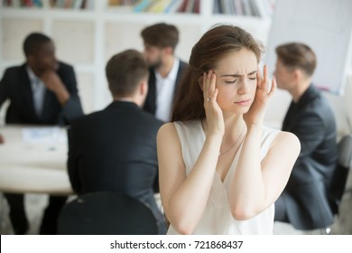 Stressed young female corporate employee having migraine at unproductive briefing. Business woman got headache from stressful meeting, coworkers not collaborating. Female executive sick from stress.