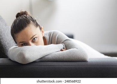 Stressed young housewife in living room