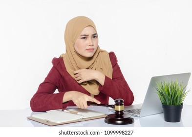 stressed young lawyer sitting working with her laptop. hand holding wooden gavel
