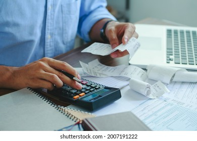 Stressed young man holding pen working on calculator to calculate business data, taxes, bills payment, Start up counting finance.accounting, statistics, and analytic research concept