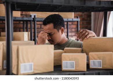 stressed young man working at home,checking packages