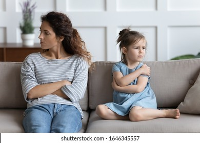Stressed young mother sitting separately with offended little preschool daughter, ignoring each other in living room. Frustrated woman not talking to stubborn kid girl, family problems concept.
