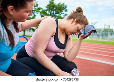 Stressed young plump female with towel and bottle of water expressing tiredness while friend comforting her