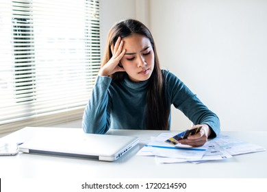 stressed young pretty woman headache looking at credit card invoice in hand and worried about bill in home office, plan money cost saving, shopping online