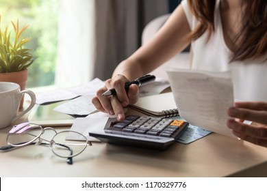 Stressed young woman calculating monthly home expenses, tax, bank account balance and credit card bills payment, Income is not enough for expenses.