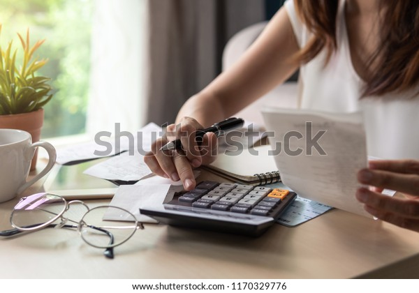 Stressed young woman calculating monthly home expenses, taxes, bank account balance and credit card bills payment, Income is not enough for expenses.