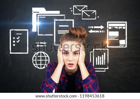 Stressed young woman in checkered shirt sitting near chalkboard with electronic documents and internet icons. Concept of information overload. Toned image