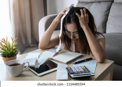 Stressed young woman checking bills, taxes, bank account balance and calculating expenses in the living room at home