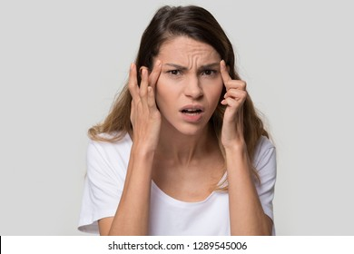 Stressed young woman confused about facial wrinkles aging skin on forehead or crows feet looking at camera isolated on studio background, upset worried girl having headache touching temples, portrait