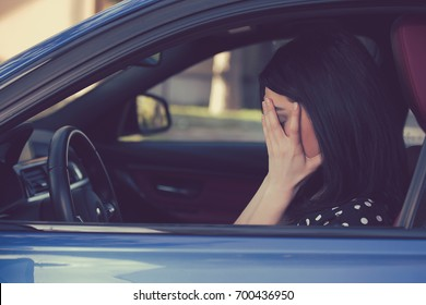 Stressed young woman driver sitting inside her car