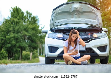 Stressed young woman frustrated woman sitting after a car breakdown at the side of the road,Accident,Cars and transportation concept