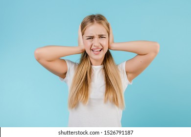 stressed young woman with headache covering ears isolated over blue