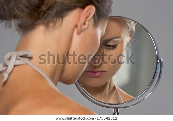 Stressed young woman looking in mirror
