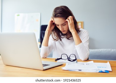 Stressed young woman sitting at desk working from home office