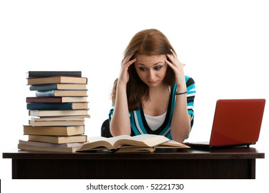 Stressed young woman sitting at a table among books and  laptop on a white background