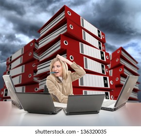 Stressed young woman using multiple computers, with piles of folders on the backgrounds