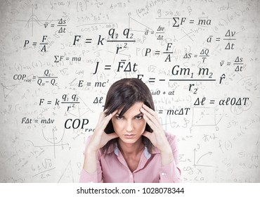 Stressed young woman wearing a pink shirt and sitting with her fingers touching her temples. A headache. A concrete wall with formula on it