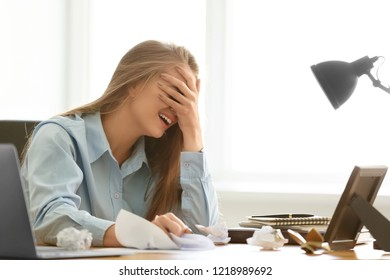 Stressed young woman at workplace