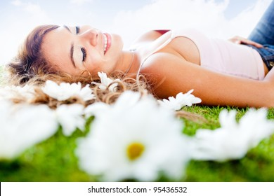Stress-free woman resting outdoors lying on the grass