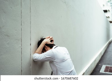 Stressful businessman cover his head with hands, headbutt the wall. Bad business concept.
