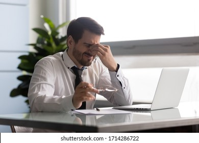 Stressful businessman taking off glasses, suffering from dry eyes syndrome after long laptop use. Exhausted employee executive manager ceo feeling eye strain, massaging nose bridge