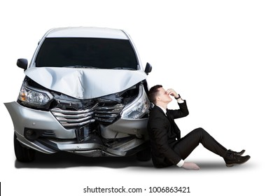 Stressful Caucasian businessman sitting near a broken car, isolated on white background
