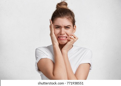 Stressful crying cute female feels miserable, has mournul expression, regret big life mistakes, looks desperately, expresses negative emotions, being very dejected. Unhappy woman with hair bun