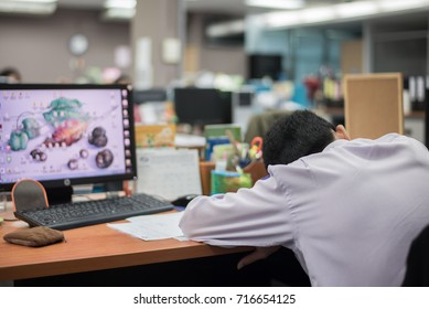 Stressful male entrepreneur sleeping on the table with computer and documents, shot in the office room