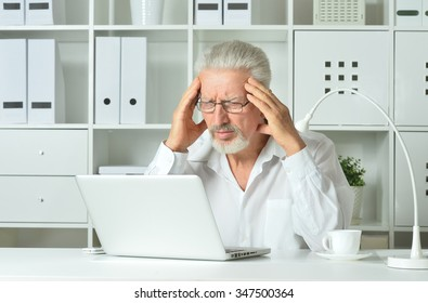 stressful Mature businessman working with laptop in office